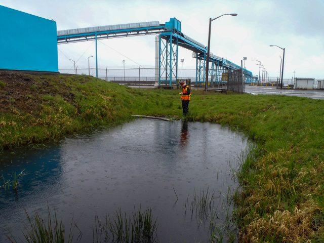 An MFA employee stormwater sampling at an industrial site